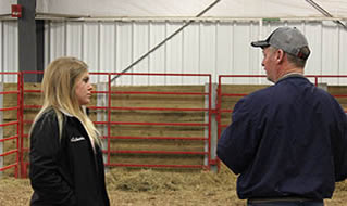 ISU student employee Michaela Friest talks with a potential buyer at the 2018 Tradition of Excellence sale hosted by ISU students at the Hansen Ag Student Learning Center.